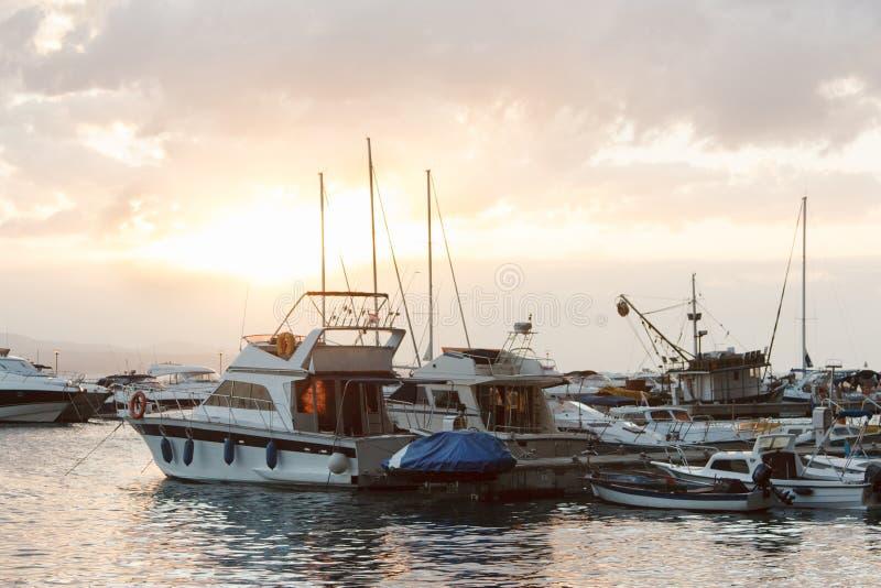 游艇在反对日落天空的海被停泊与云彩, 免版税库存图片