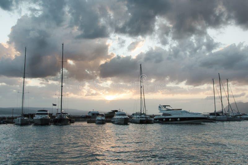 游艇在反对日落天空的海被停泊与云彩 库存图片