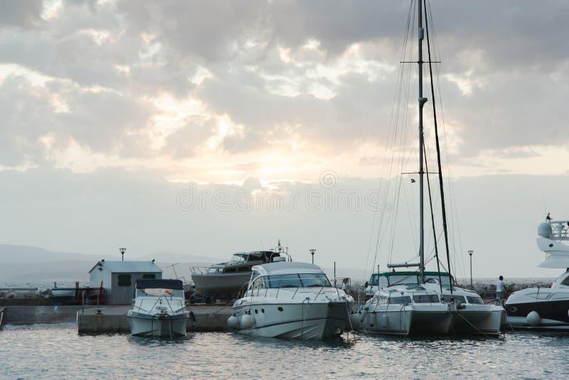 游艇在反对日落天空的海被停泊与云彩 免版税库存图片