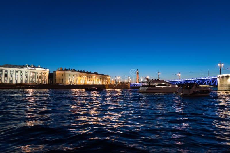 游艇在晚上临近宫殿桥梁和Vasilievsky海岛在圣彼德堡,俄罗斯 库存照片