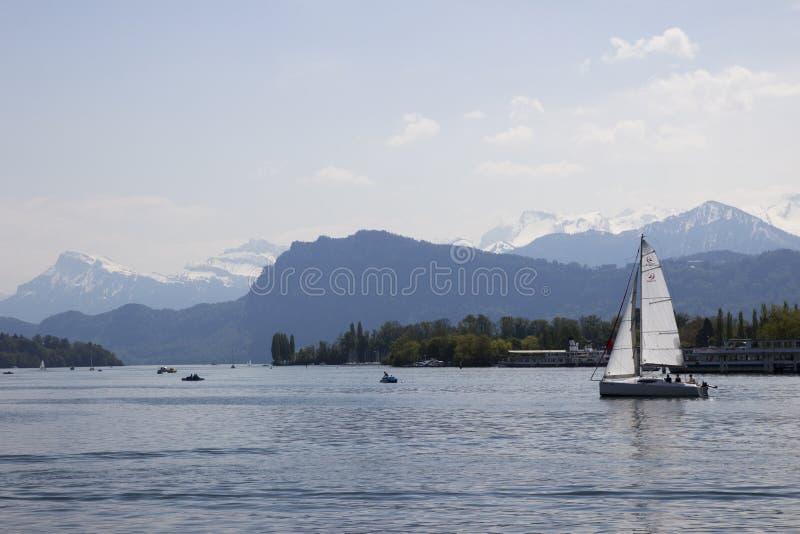 游艇在水航行 瑞士城镇 美丽的山 美丽的天空 大海 库存图片