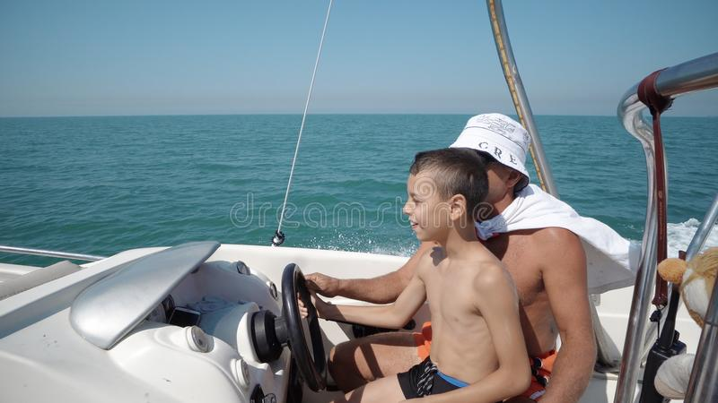 游艇在游艇方向盘的上尉手 教一个小男孩如何的地方人驾驶在parasail肾上腺素乘驾的一条游艇小船 图库摄影