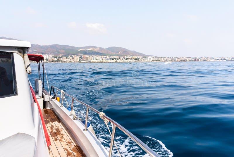 游艇或私有豪华小船乘驾 航行在海或海洋有汽艇或风船的 从甲板的看法海岸的 免版税库存图片