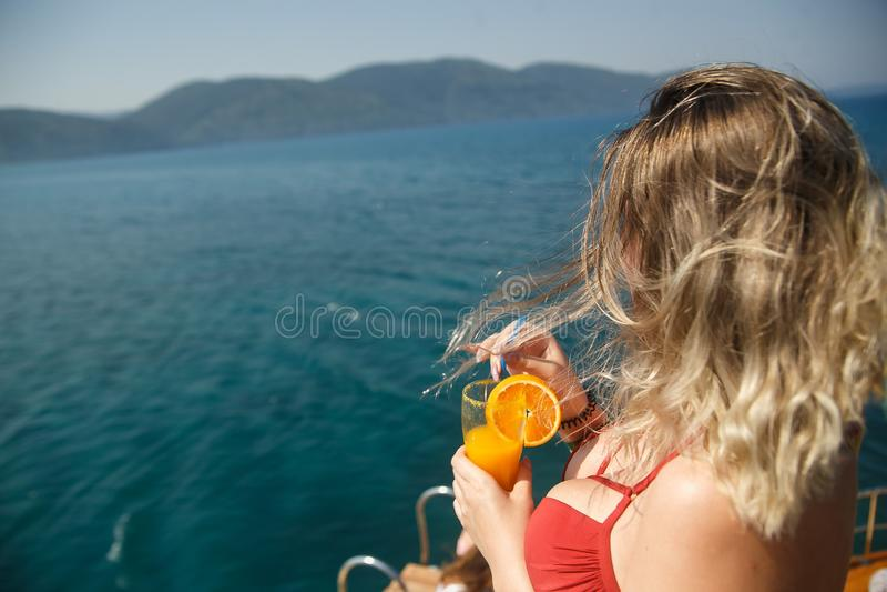 游艇的愉快的大乳房妇女 女孩的夫人拿着橙色新饮料的珊瑚比基尼泳装的 冷饮和新鲜的蓝绿色海 库存照片