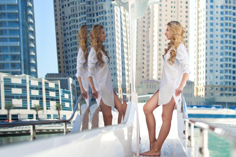 游艇的白肤金发的女孩,摩天大楼作为背景 免版税图库摄影