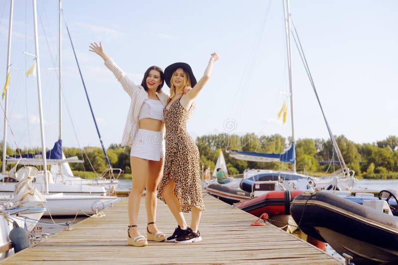 游艇,帆船背景的两个女孩是微笑,看照相机 一个帽子和金发碧眼的女人的浅黑肤色的男人礼服的 库存照片