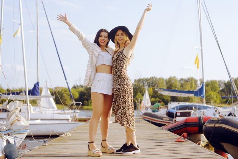 游艇,帆船背景的两个女孩是微笑,看照相机 一个帽子和金发碧眼的女人的浅黑肤色的男人礼服的 免版税库存照片