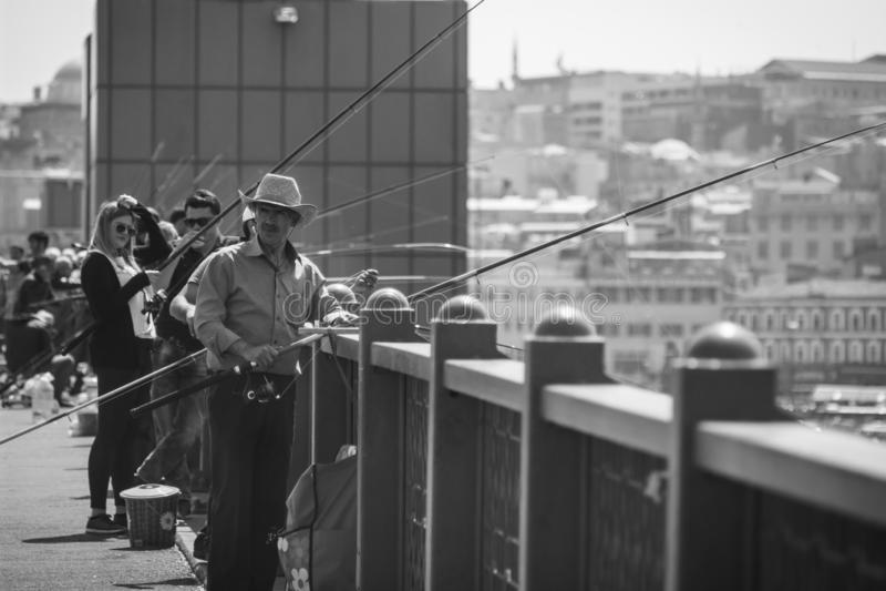 游览在加拉塔大桥的人钓鱼和游人 免版税图库摄影