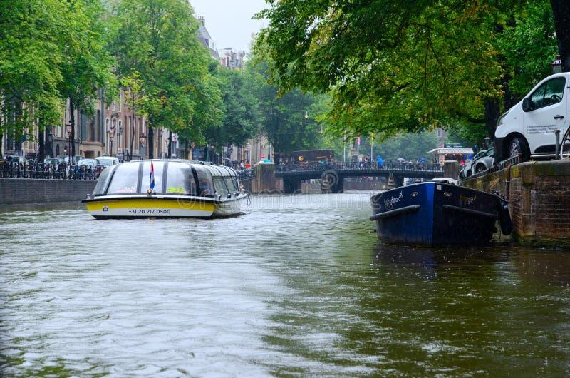 游览在运河的游船在市中心,下雨天,阿姆斯特丹,荷兰 库存图片