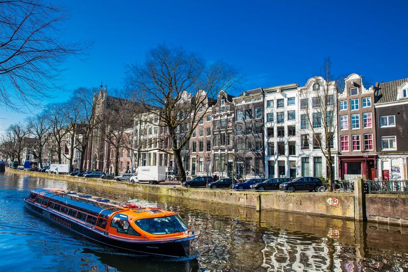 游览在阿姆斯特丹运河附近的旅游小船 图库摄影