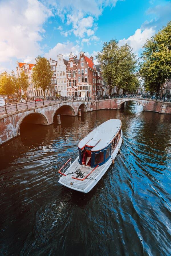 游览小船在著名荷兰运河在一个晴天,传统荷兰桥梁,中世纪房子 阿姆斯特丹荷兰 免版税库存照片