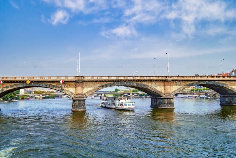 游轮在伏尔塔瓦河河的桥梁下 布拉格,捷克共和国 免版税图库摄影