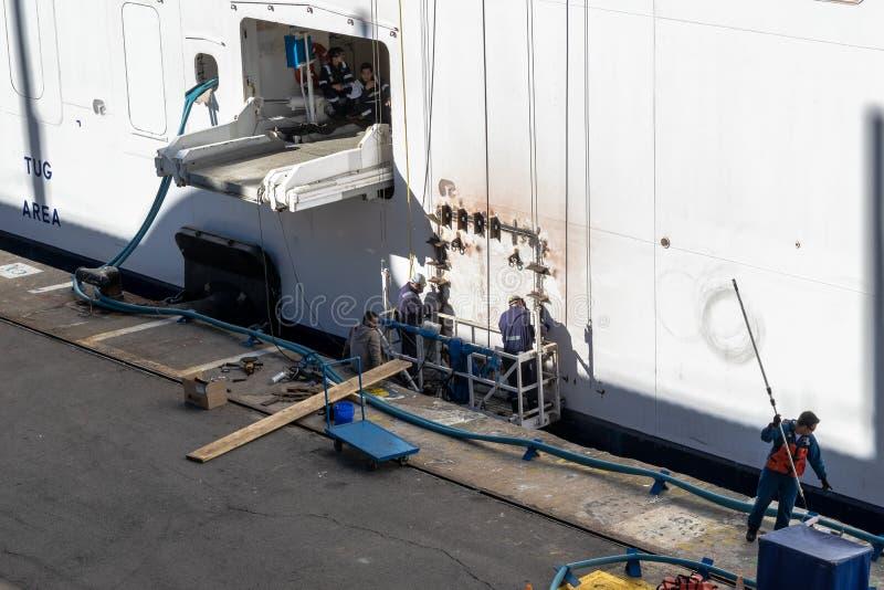 游轮维修组/执行焊接的工作修理和绘在靠码头的船外部的猛拉地区附近的职员/工作者  免版税图库摄影