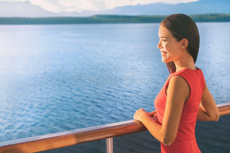 游轮阿拉斯加旅行豪华小船的假期妇女 看海洋的日落视图从阳台的亚裔典雅的夫人 免版税库存照片