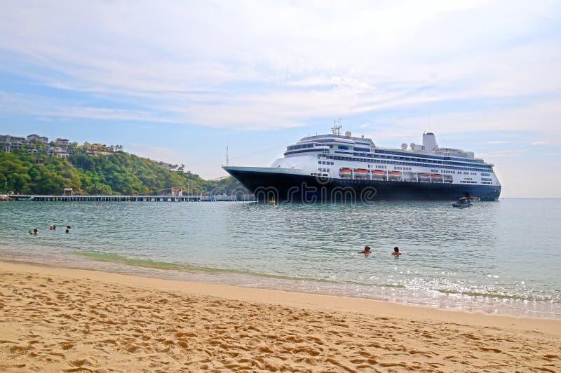 游轮靠码头在圣克鲁斯海湾,Huatulco,墨西哥 游泳者和海滩 免版税库存图片