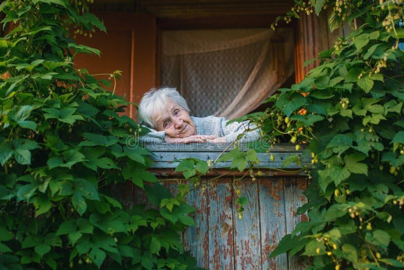游廊的一名年长妇女在绿叶中 自然 免版税库存照片