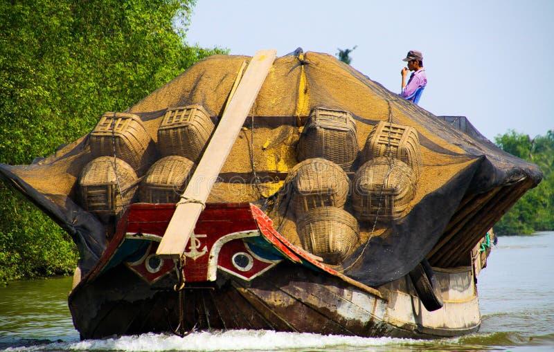 湄公河三角洲,越南:12月30日 2014年:有典型的风格化弓眼睛的被超载的sampan样式小船 库存图片