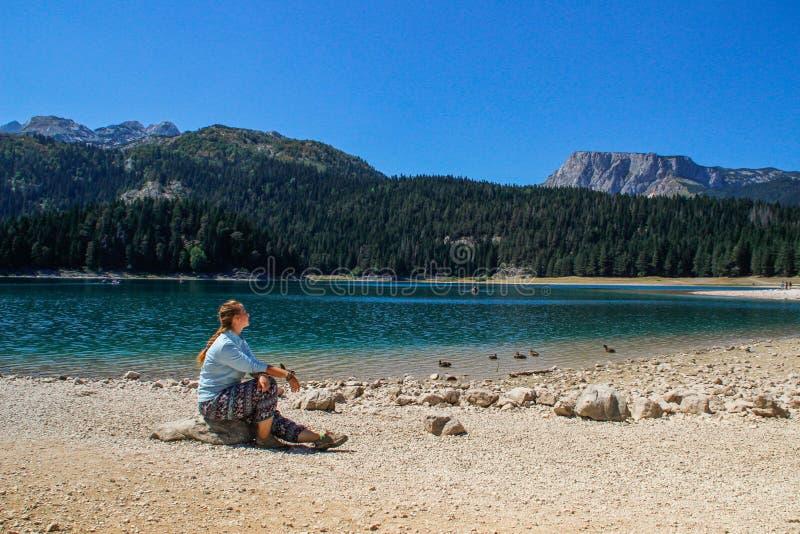 湖、杉木森林和山的绿松石水 与自然女孩游人的惊人背景坐海滩 免版税库存图片