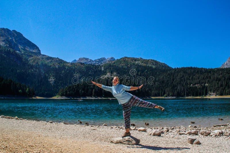 湖、杉木森林和山的绿松石水 与自然旅游女孩欣喜的惊人背景在海滩 库存照片
