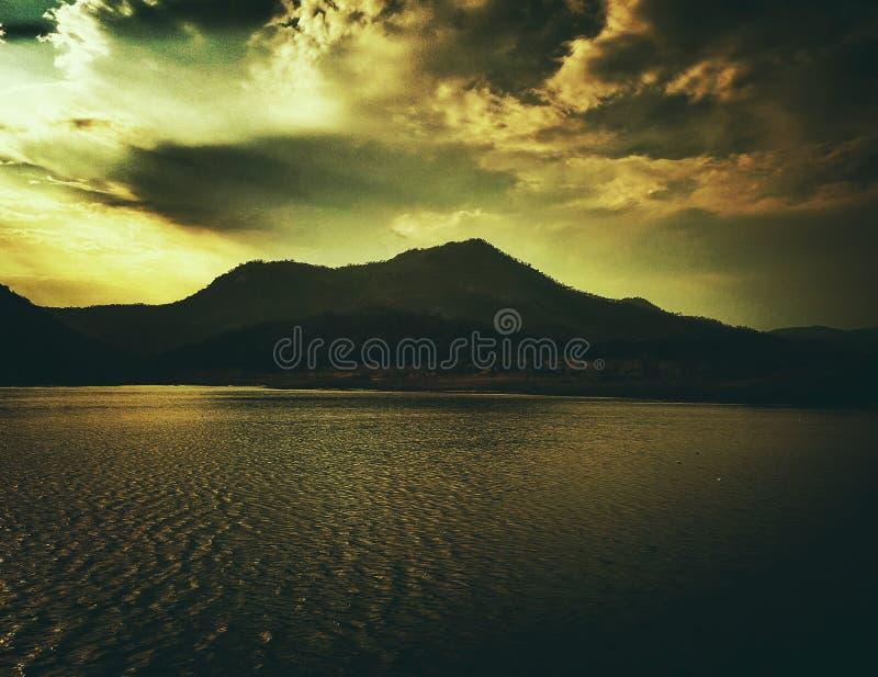 湖、水小山和日落天空的一张黑暗的喜怒无常的美好的图片 免版税库存照片