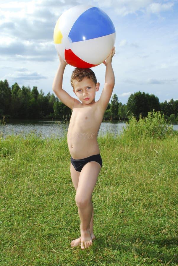 湖使用与一个可膨胀的球的一个小男孩 免版税库存照片