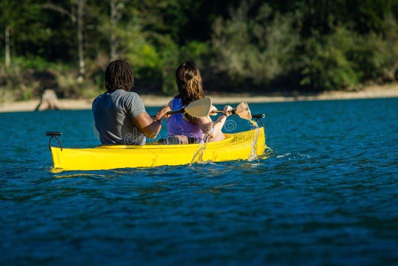 湖划皮船的夫妇 免版税库存照片