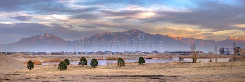 湖和家反对被日光照射了山在破晓 图库摄影