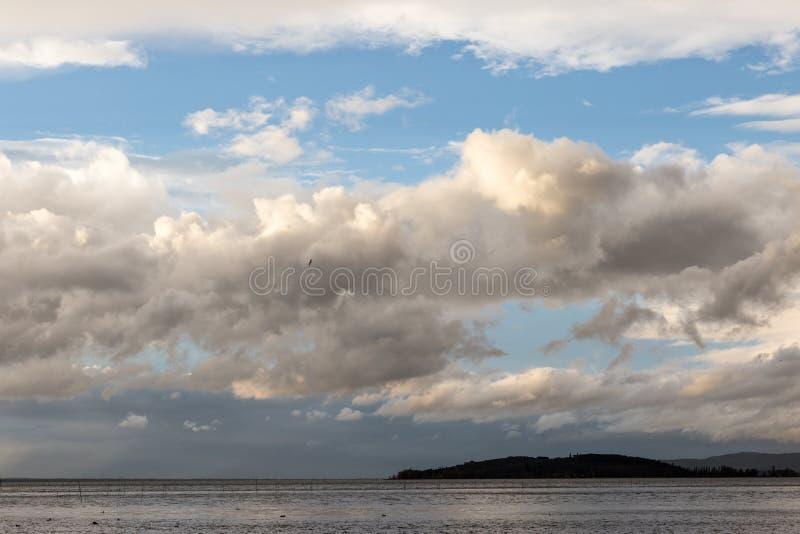 湖在与大云彩的喜怒无常的天在海岛和蓝天 免版税库存图片