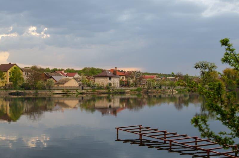 湖在有天空的反射的一个村庄在雨前的 免版税库存图片