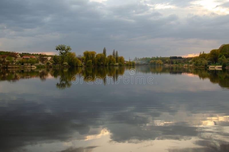 湖在有天空的反射的一个村庄在雨前的 图库摄影