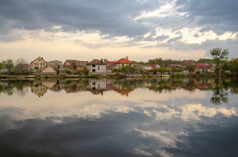 湖在有天空的反射的一个村庄在雨前的 库存图片