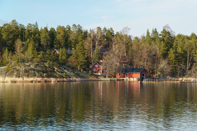 湖岸的斯堪的纳维亚传统红色木房子在夏天 乡下风景在芬兰 库存图片