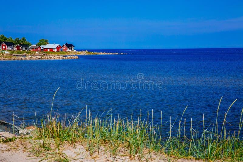 湖或沿海渔村的红色木房子在芬兰 免版税图库摄影