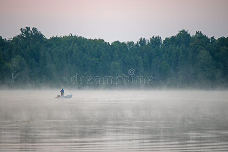 湖的孤立渔夫在黎明前 免版税库存照片
