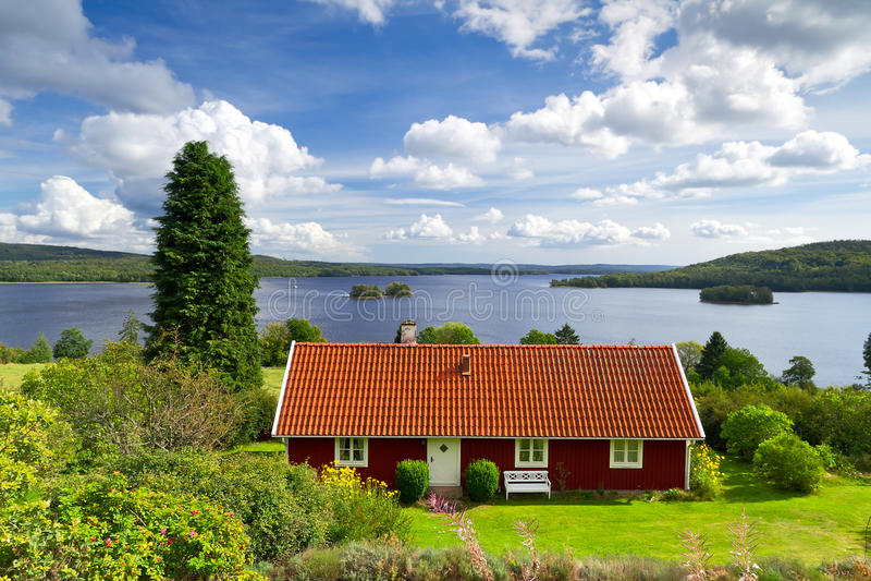 湖的瑞典村庄房子 免版税库存照片