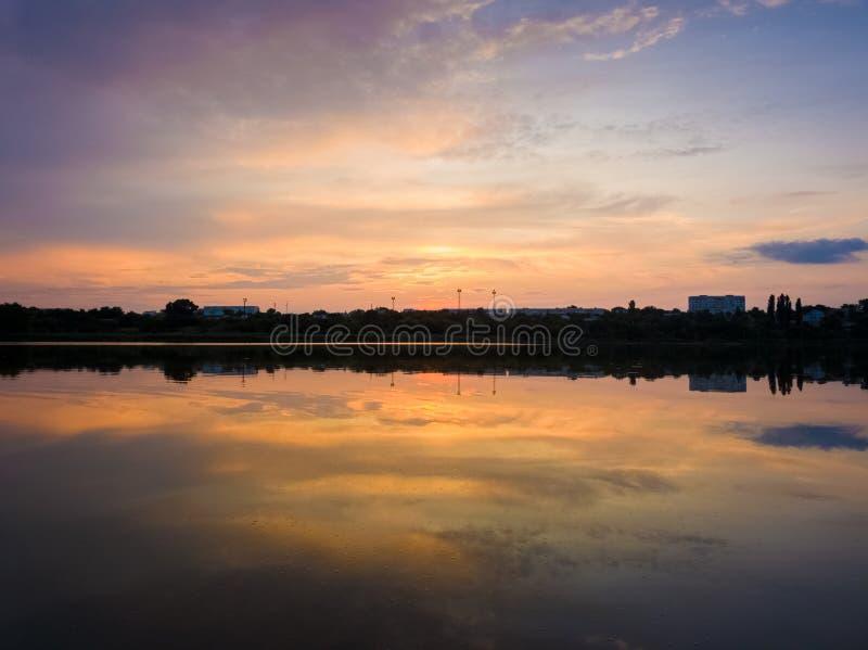 湖表面上反射的五颜六色日落云彩相称 田园诗夏天晚上,在乡下池塘附近的自然场面与 库存照片