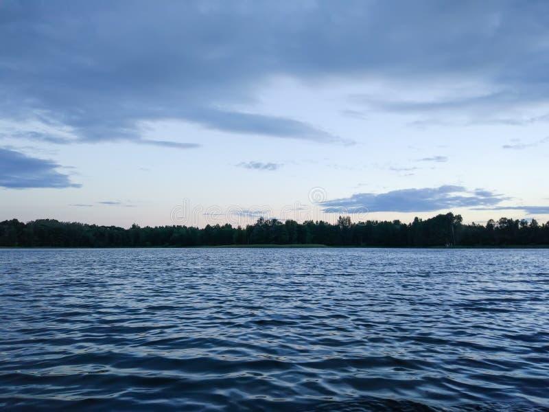 湖表面晚上在拉脱维亚,东欧 与水和森林的风景 图库摄影