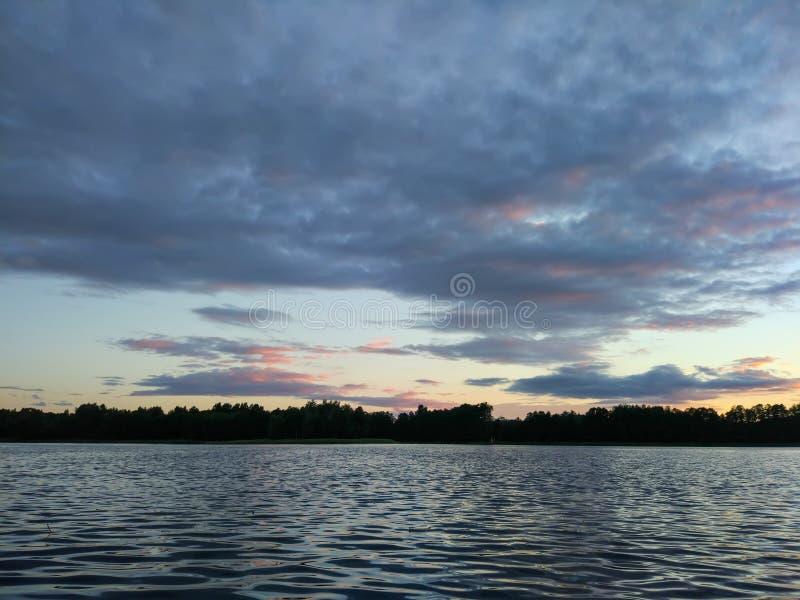 湖表面晚上在拉脱维亚,东欧 与水和森林的风景 免版税库存图片