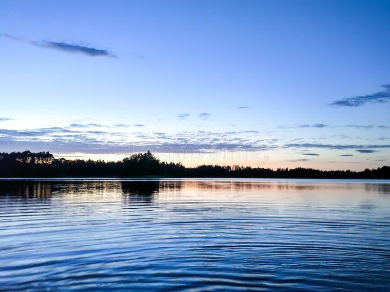 湖表面晚上在拉脱维亚,东欧 与水和森林的风景 免版税图库摄影