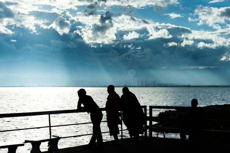 湖视图意想不到的风景在黄昏的、抽象云彩和光束发光在湖和山背景的,修士和人们 免版税库存照片