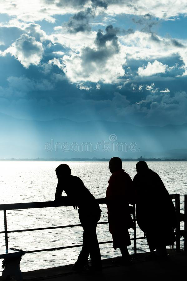 湖视图意想不到的风景在黄昏的、抽象云彩和光束发光在湖和山背景的,修士和人们 库存图片