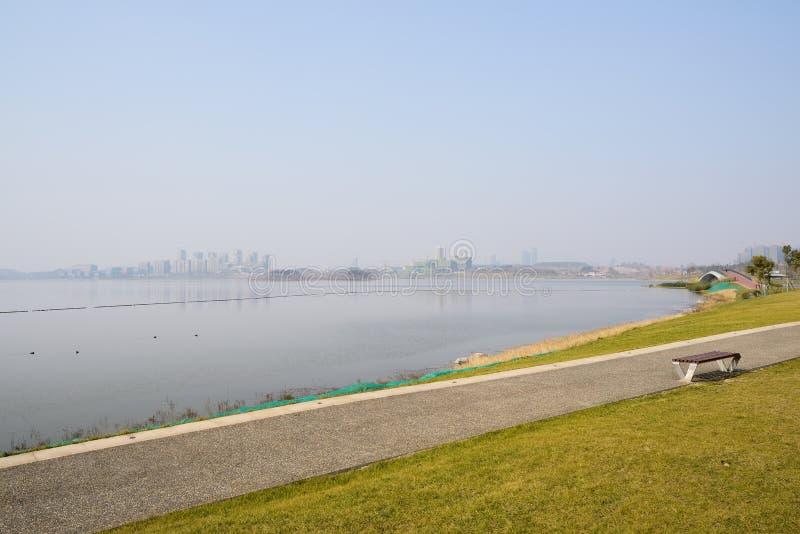 湖边道路在晴朗的冬天下午,天府新的地区的草坪 库存照片