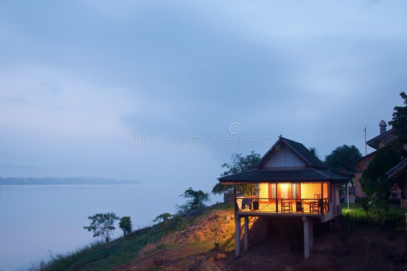 湖银行的房子在黎明 免版税库存照片