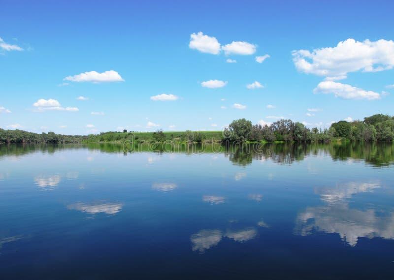 湖,有树的森林,蓝天,云彩 免版税库存图片