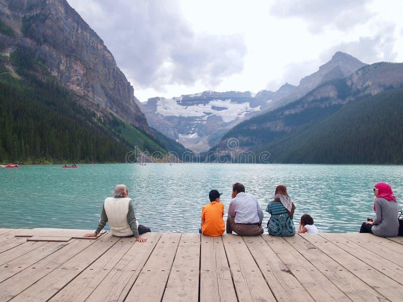 湖Lousie -人们坐与mountian后面的水 免版税图库摄影