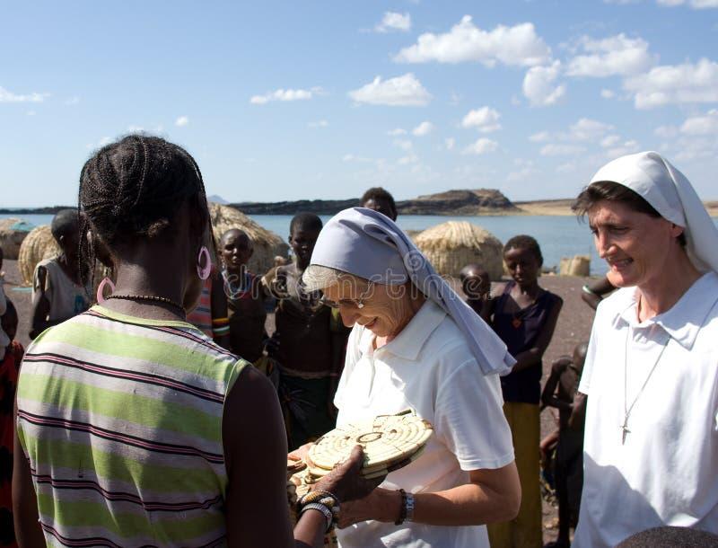 基督教会购买工艺品非洲人部落的尼姑 图库摄影