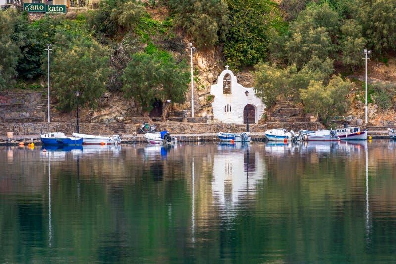 湖Voulismeni在贴水帕帕佐普洛斯,有五颜六色的大厦的一个美丽如画的沿海城市在口岸附近 免版税库存图片
