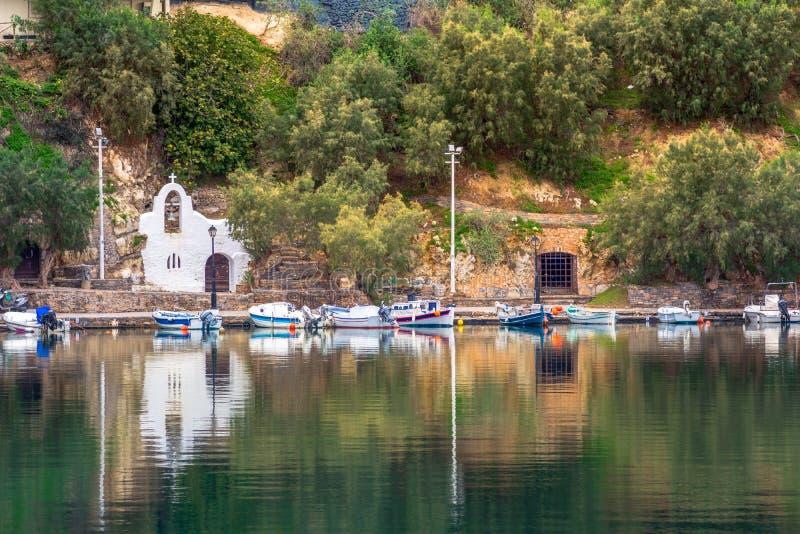 湖Voulismeni在贴水帕帕佐普洛斯,有五颜六色的大厦的一个美丽如画的沿海城市在口岸附近 免版税图库摄影