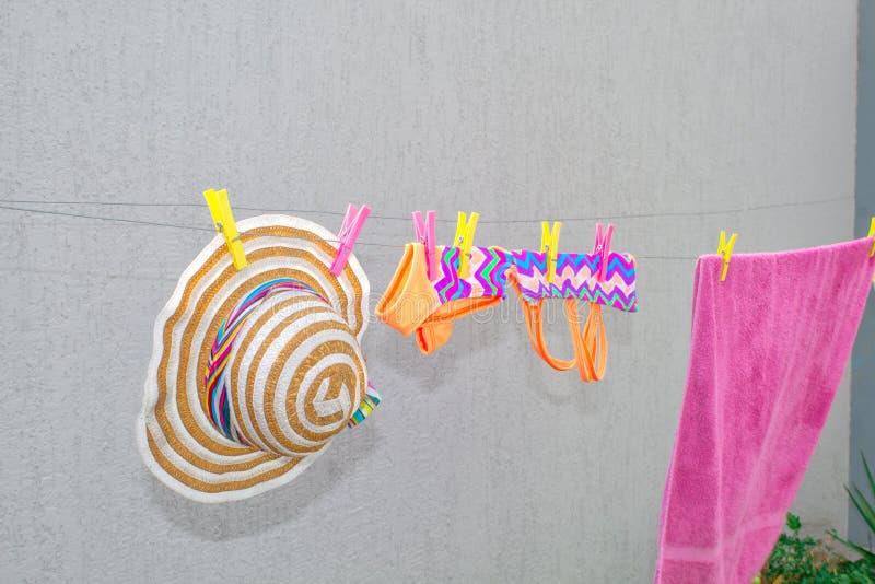 湿儿童的在晒衣夹的泳装和帽子吊和干燥 免版税库存图片