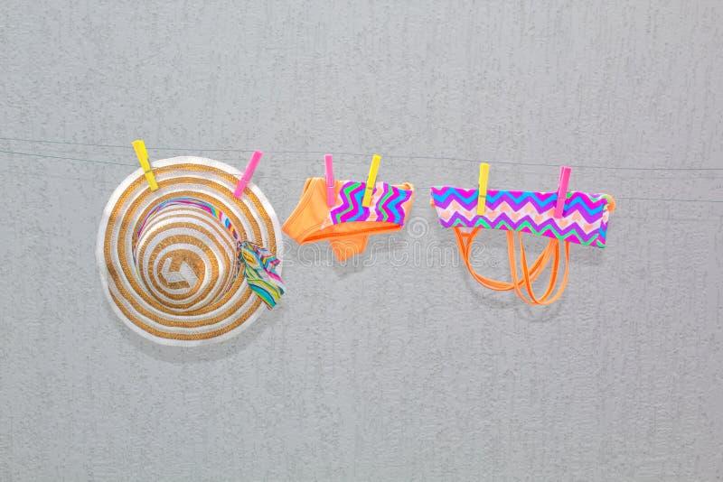 湿儿童的在晒衣夹的泳装和帽子吊和干燥 免版税库存照片